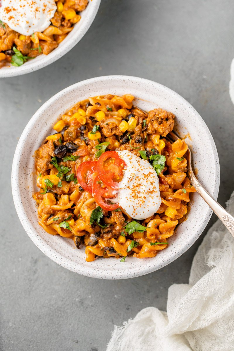 a white bowl of creamy vegan taco pasta and sour cream and tomatoes on top by sweet simple vegan