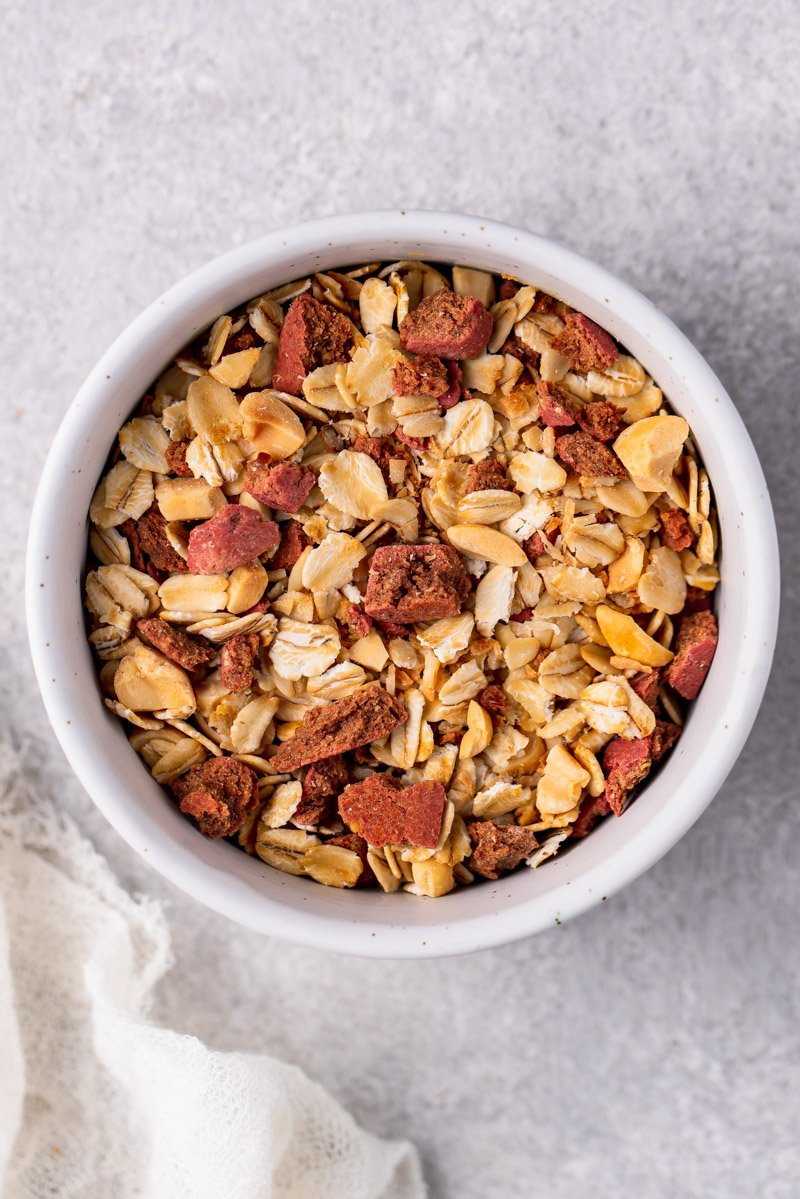 overhead image of granola in bowl with dog treats