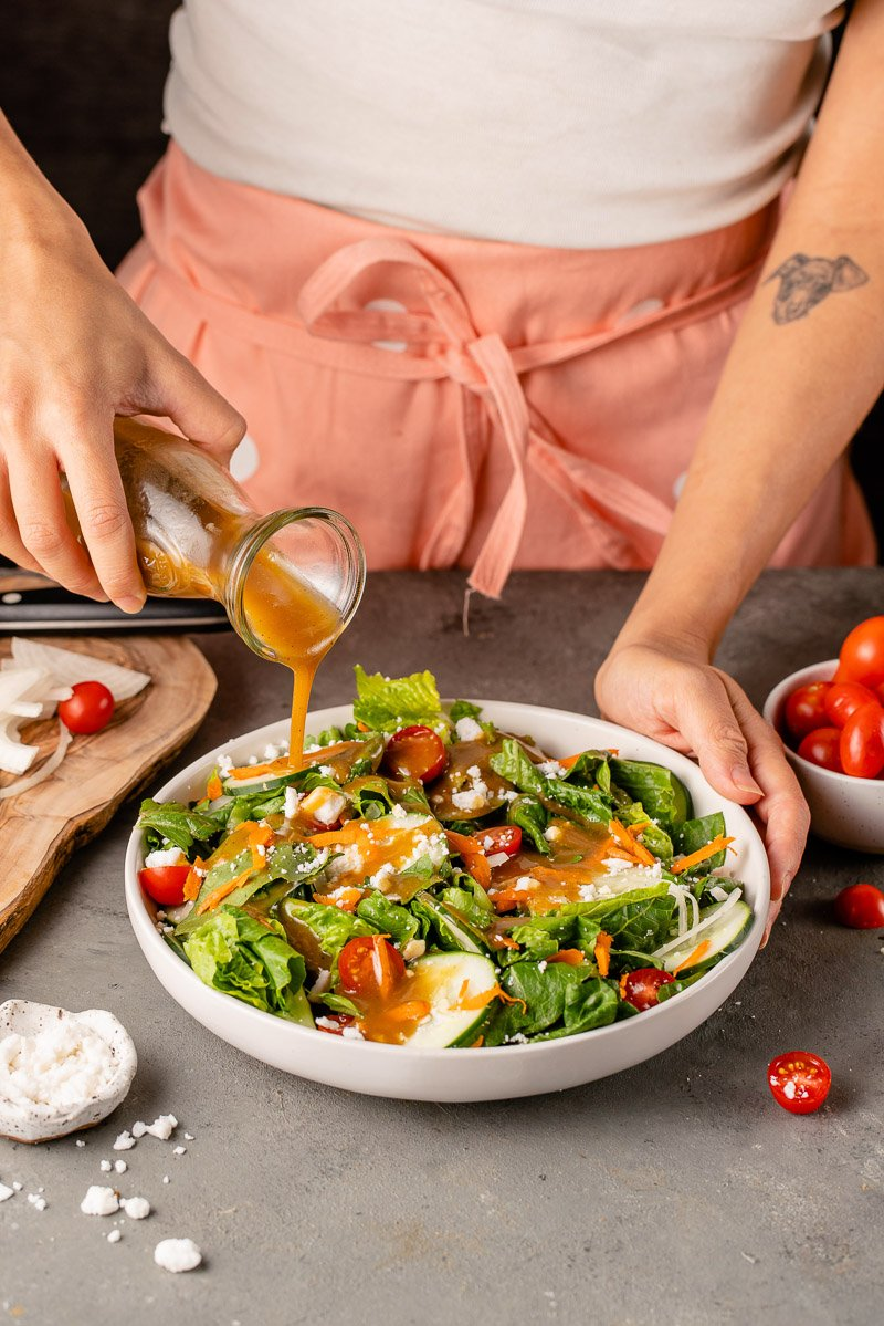 up-close lifestyle image of salad being dressed with balsamic vinaigrette