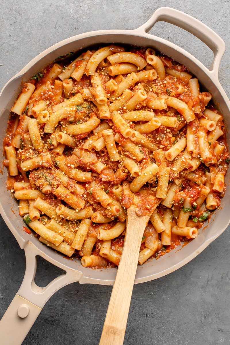 pasta in an our place pan with roasted tomato sauce and vegan parmesan