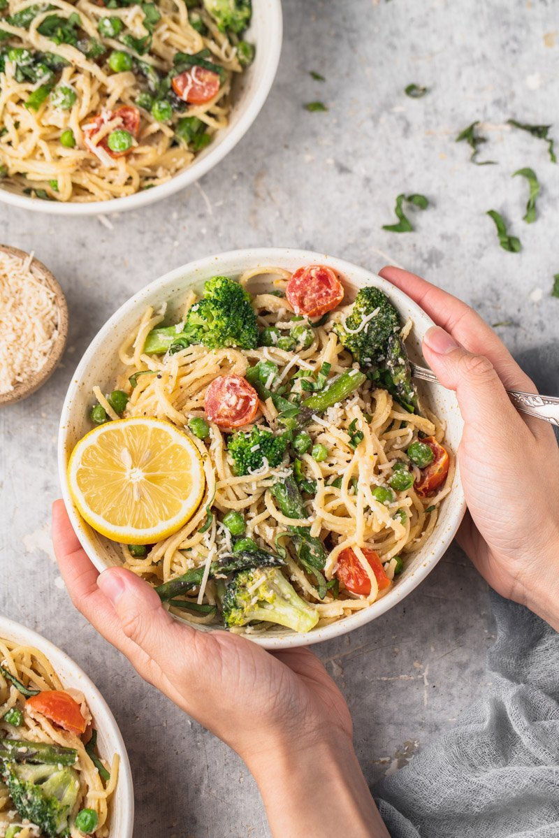 overhead image of pasta primavera in a bow being help with hands and llemon