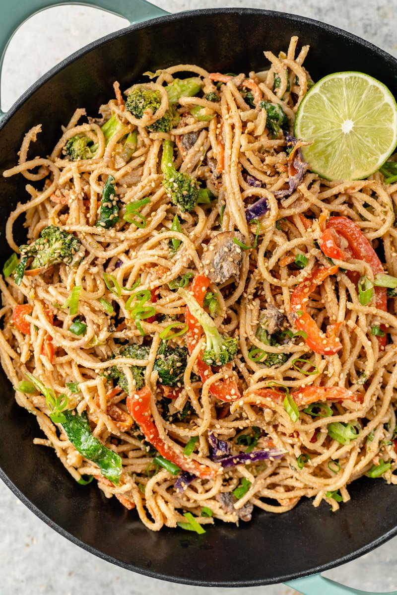 close up image of vegetable stir fry with peanut sauce in a wok