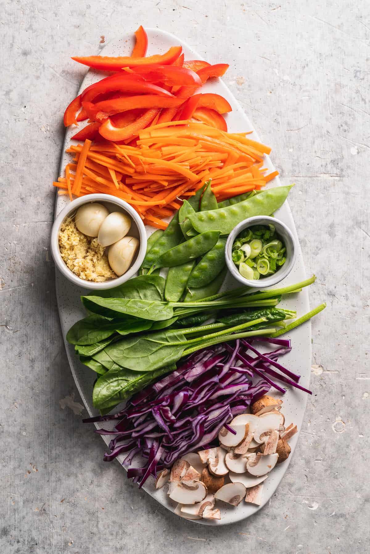 overhead image of stir fry ingredients on white platter