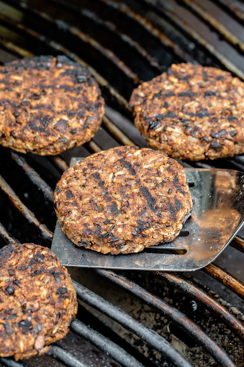 a spatula with a charred veggie burger on a grill