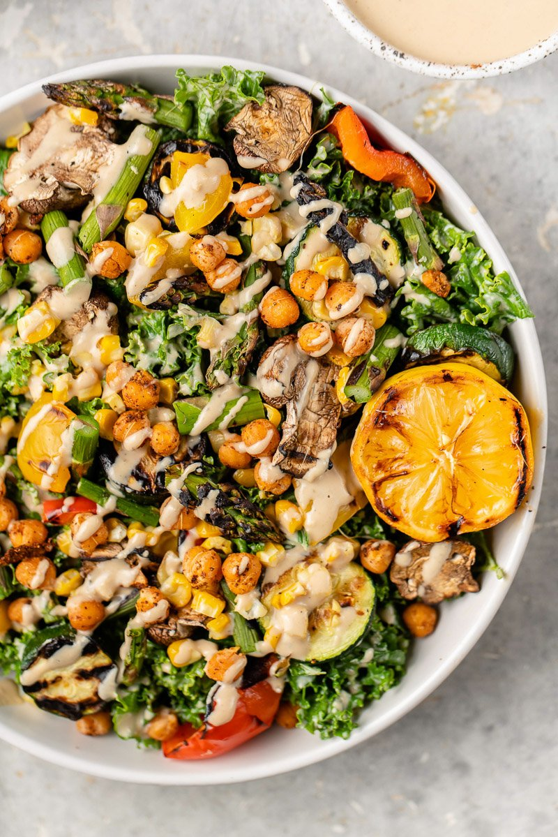 macro image of grilled vegetable salad with chickpeas and tahini dressing from above