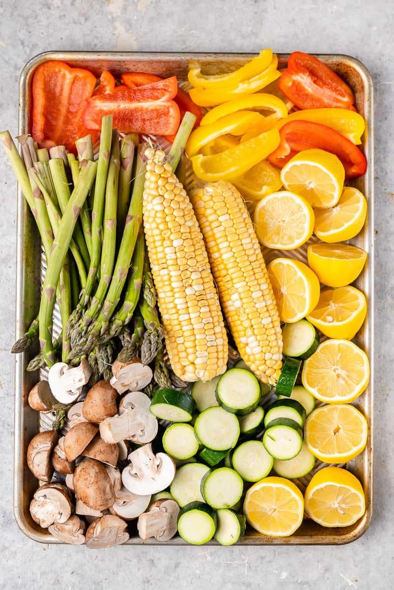overhead image of uncooked veggies on baking sheet