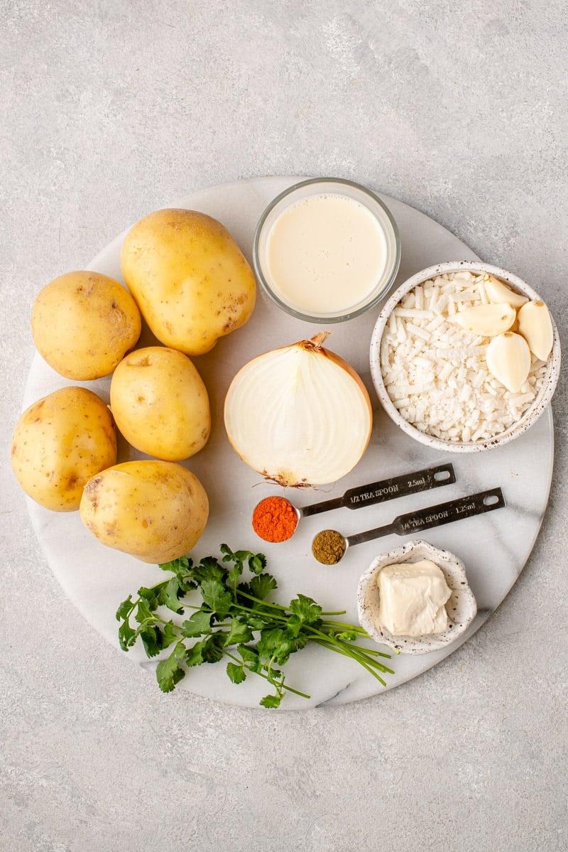 Vegan ingredientd for locro de papa on a marble board