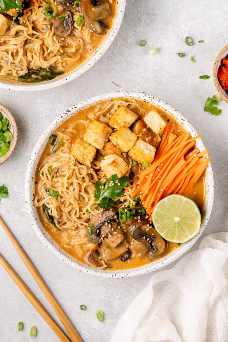 a white bowl of one pot red curry ramen on a gray board by sweetsimplevegan