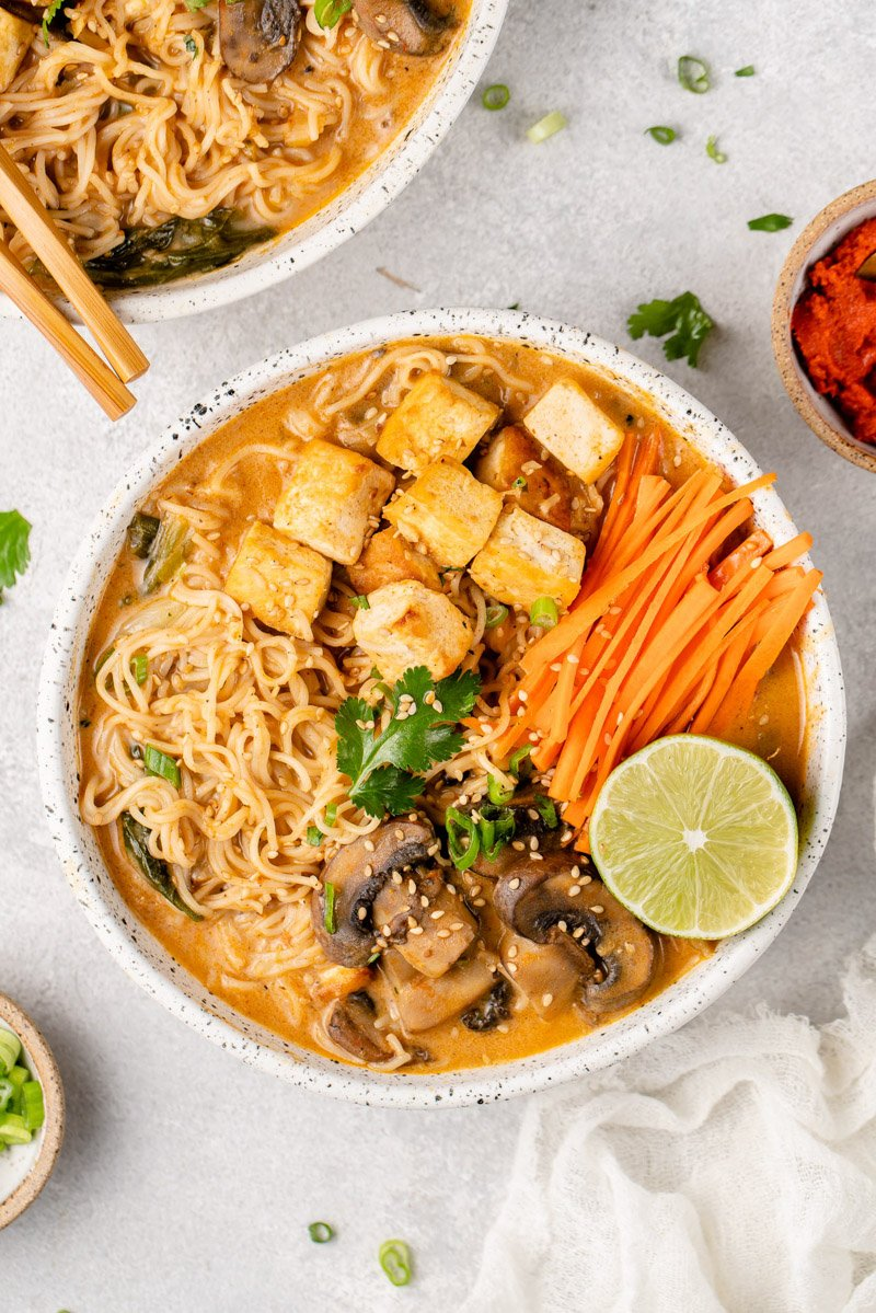 a white bowl of one pot red curry noodle soup on a gray board by sweetsimplevegan