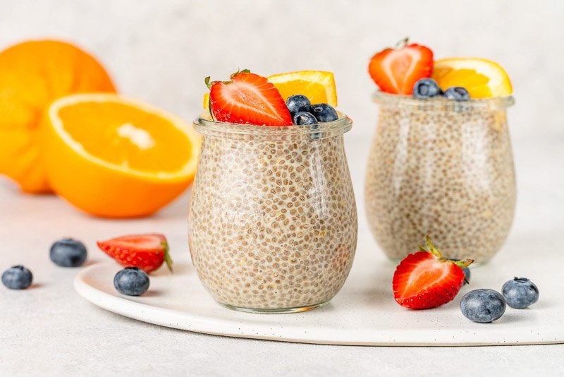 horizontal image of orange creamsicle chia pudding in glass jars topped with fruit.