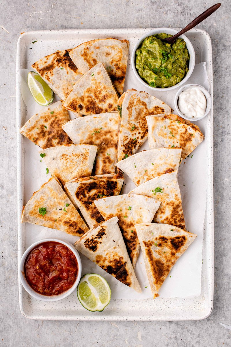 overhead image of potato & bean quesadillas in tray with salsa and guacamole