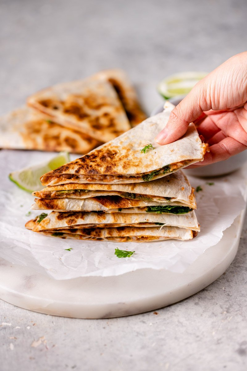 stacked slices of potato and bean quesadillas with one being picked up