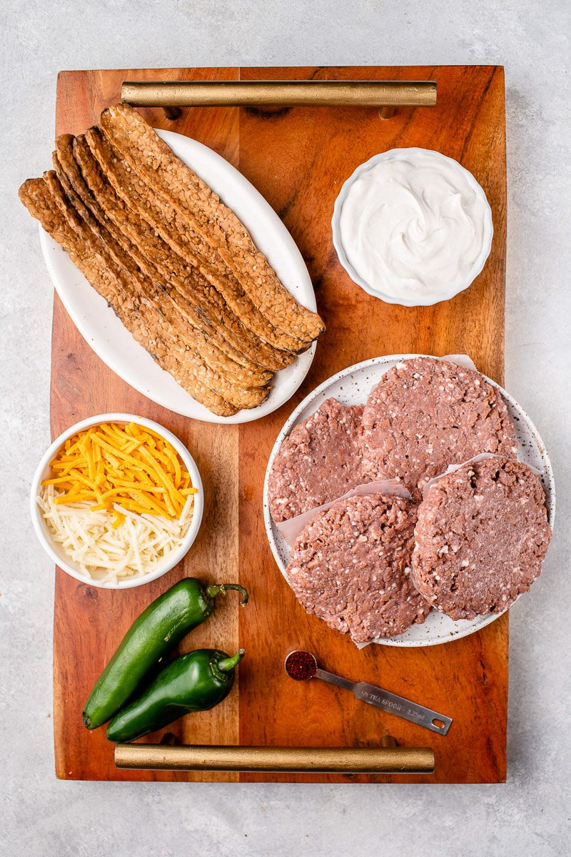 overhead image of ingredients for stuffed vegan jalapeño popper burgers on wooden tray