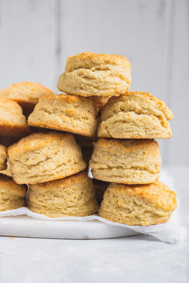 a pile of vegan buttermilk biscuits on parchment paper
