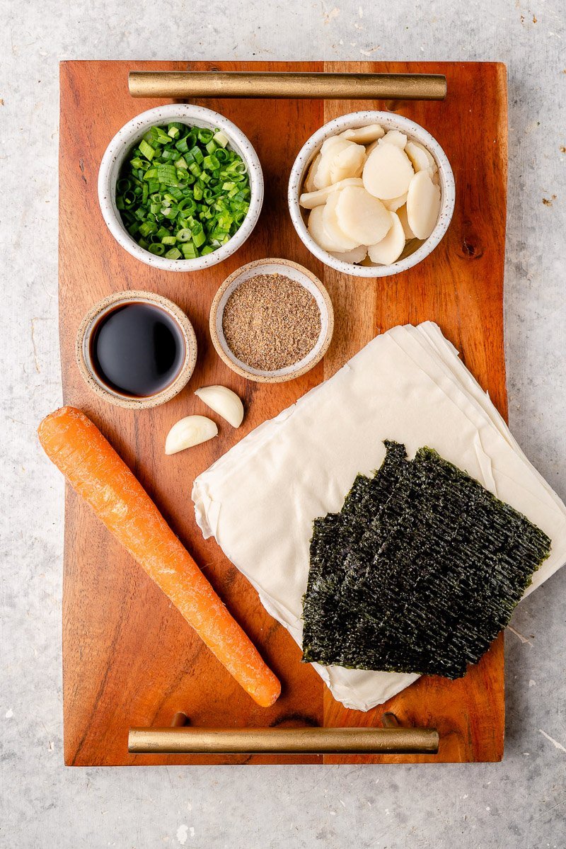 overhead image of ingredients for lumpiang shanghai on wooden tray by sweet simple vegan