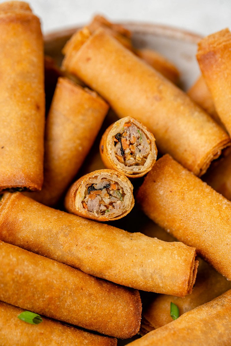macro image of lumpiang shanghai cut in half in bowl surrounded by more by sweet simple vegan