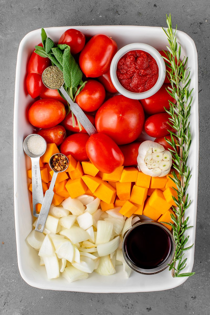 ingredients for butternut squash tomato sauce in a white casserole dish