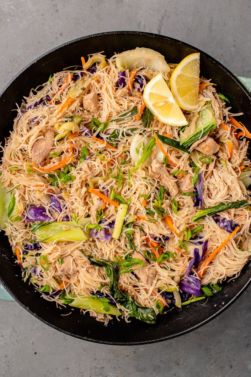 overhead image of vegan filipino pancit bihon with chicken in a wok with lemon