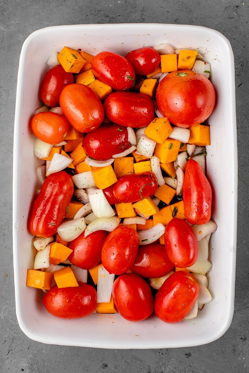 a white casserole dish with butternut squash, tomatoes, garlic, onions herbs, and red wine