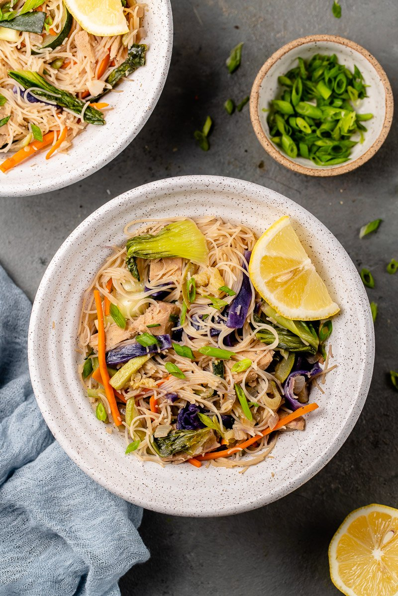 overhead image of bowl of pancit with lemon wedge and green onions on the side