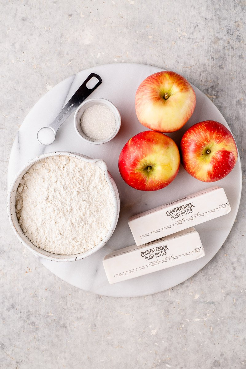 ingredients for vegan apple galette on a white marble board