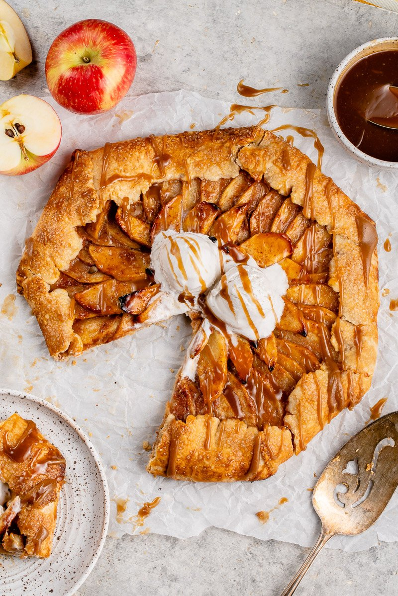 sliced vegan apple galette with vanilla ice cream and caramel sauce on a white board