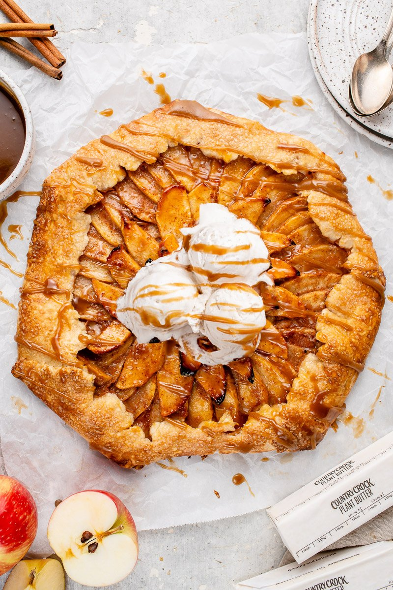 vegan apple galette with vanilla ice cream and caramel sauce on a white board