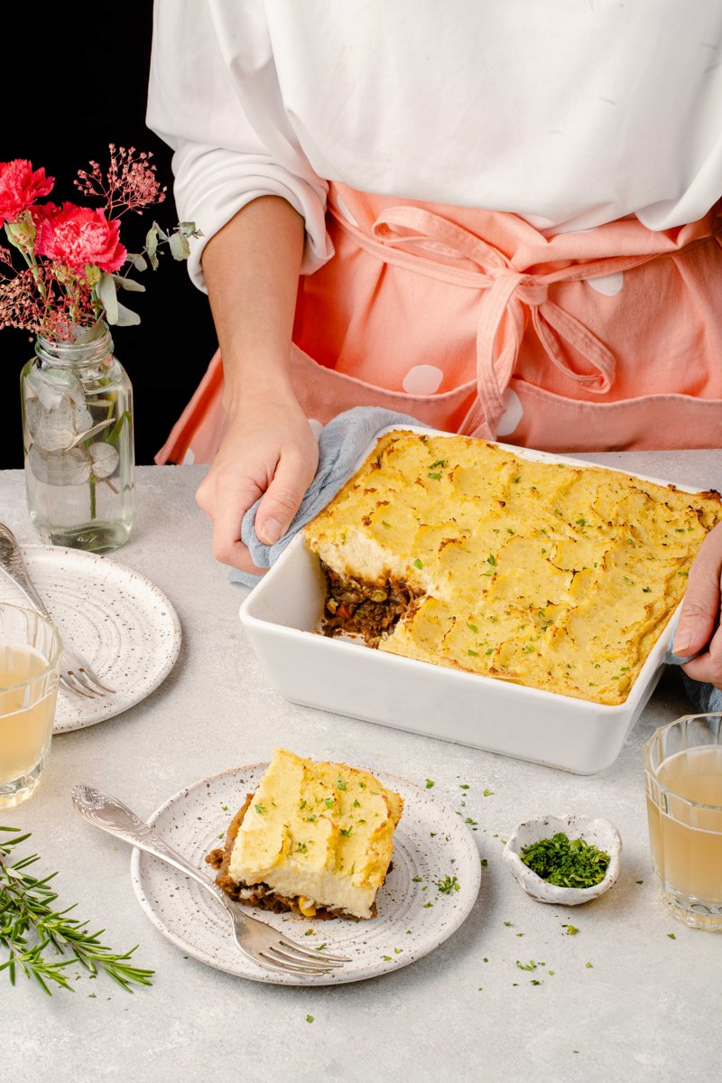 lifestyle image holding shepherds pie baking dish with piece taken out of it
