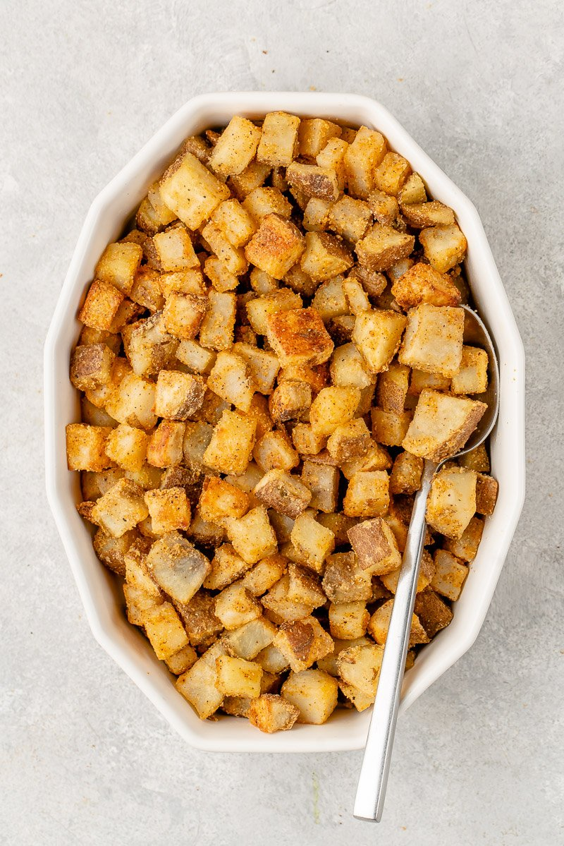 overhead image of crispy fiesta potatoes in baking dish with spoon