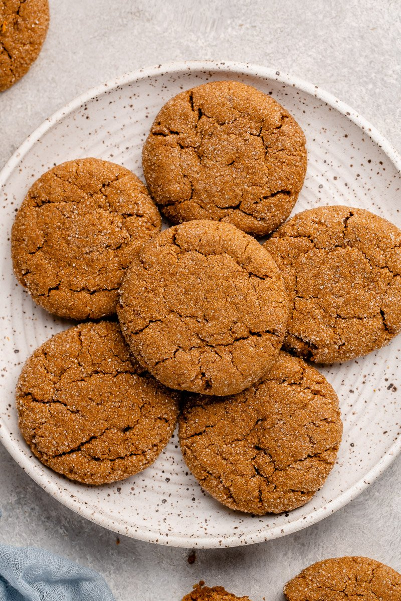 overhead shot of vegan ginger molasses cookies on a white speckled plate with a blue towel
