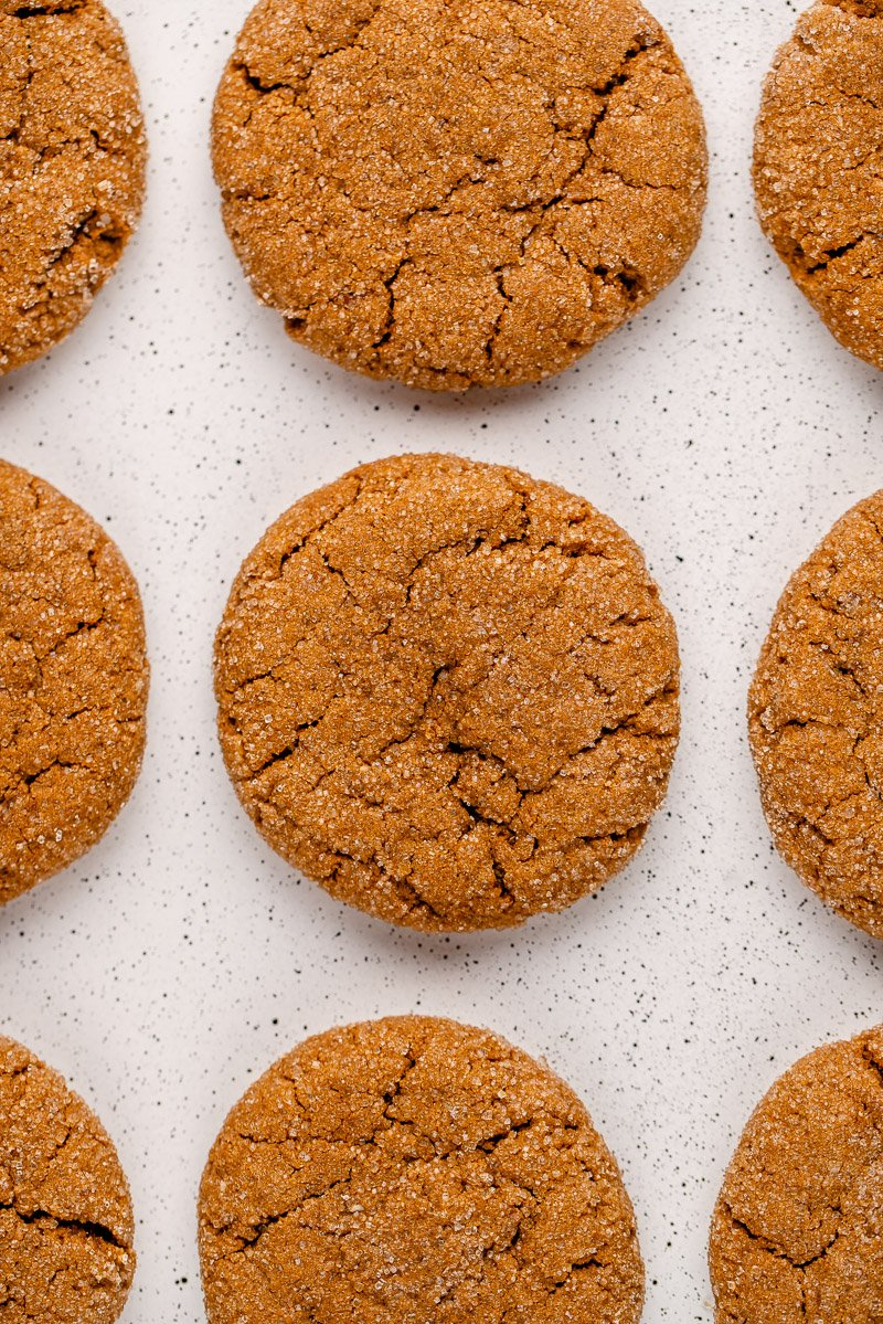 overhead shot of vegan ginger molasses cookies on a white speckled tray