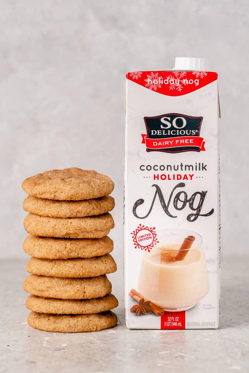 a stack of snickerdoodles next to a carton of vegan eggnog