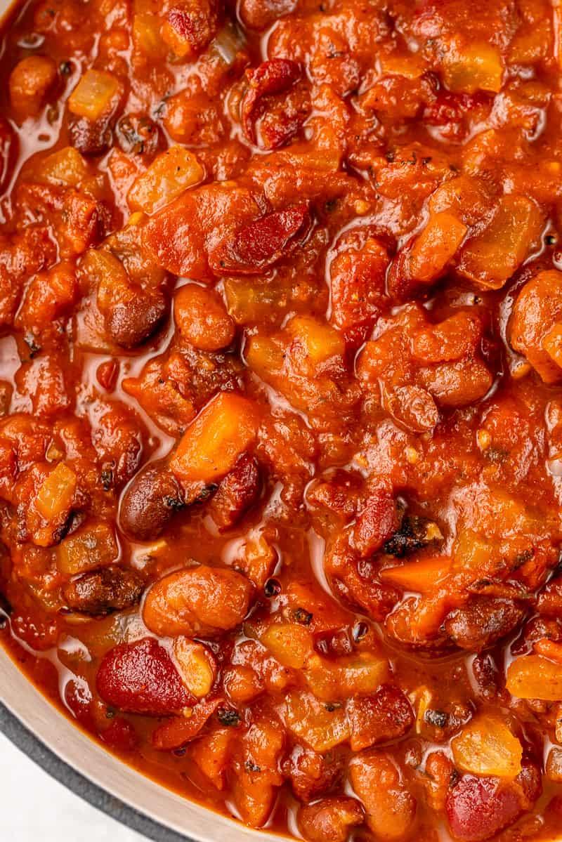 a close up shot of vegan chili in a white pot