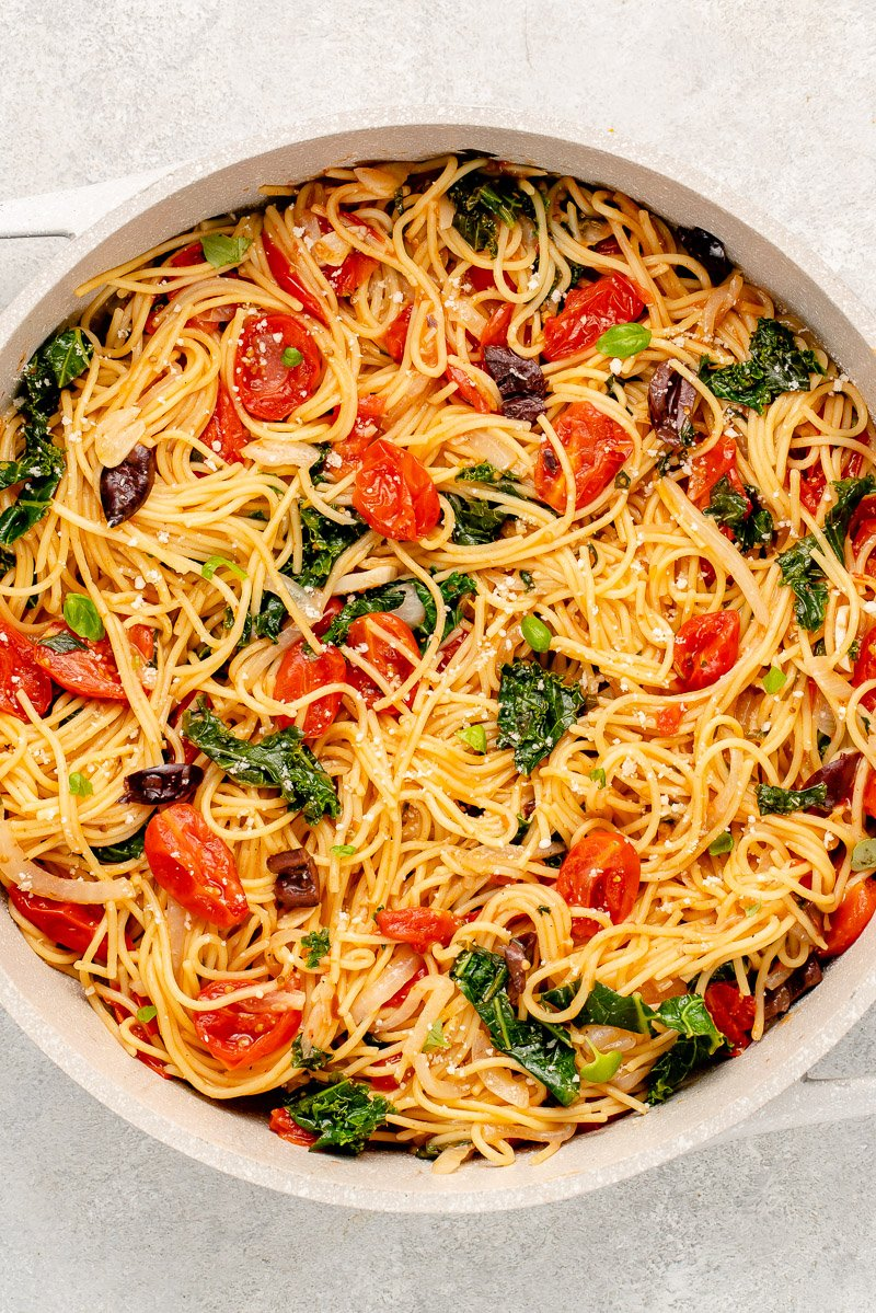 vegan pasta in a pot with tomatoes, kale, olives, basil and parmesan