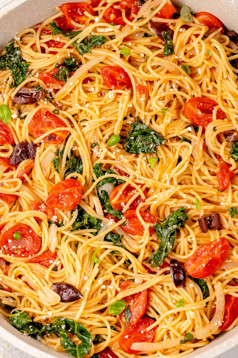 close up of vegan pasta in a pot with tomatoes, kale, olives, basil and parmesan