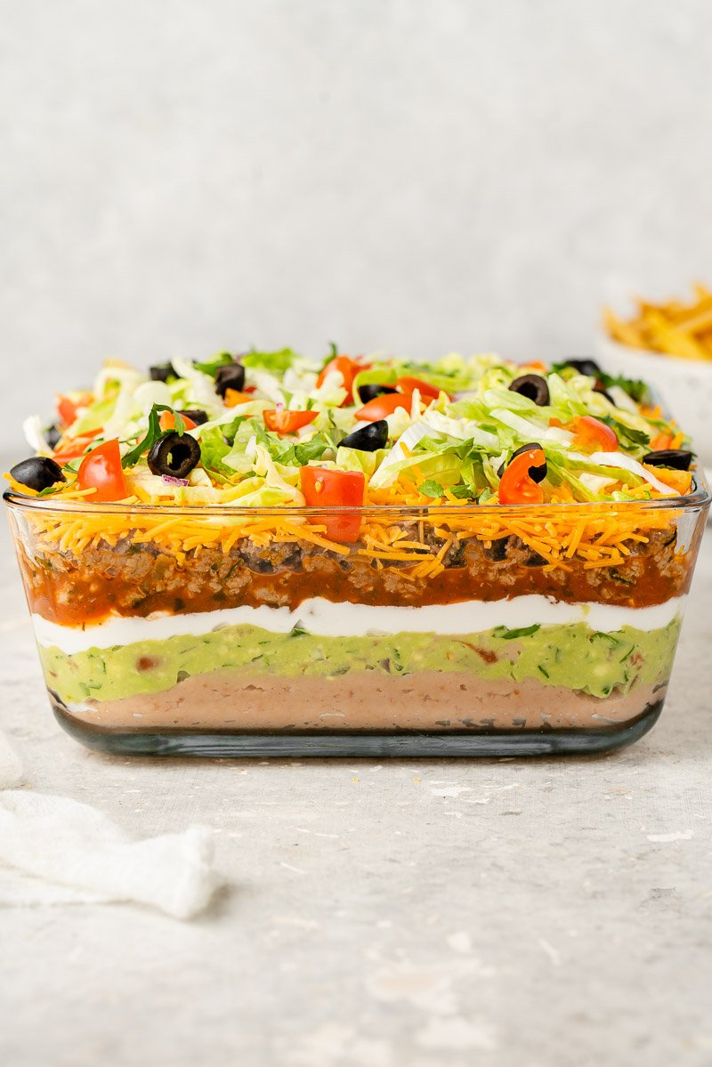 side shot of vegan 7 layer dip in a glass pyrex dish with chips in a bowl and white towel