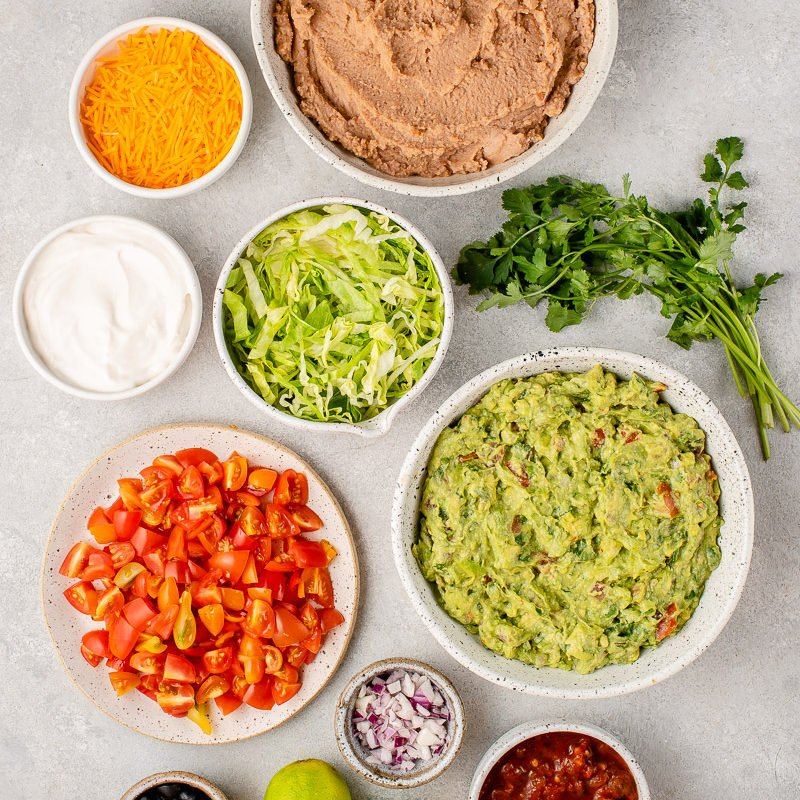 ingredients for a vegan 7 layer dip on a gray board