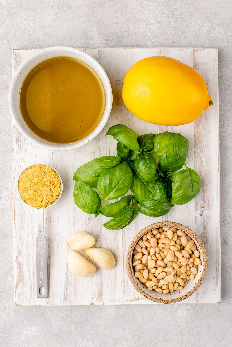 Ingredients to make pesto in a white cutting board