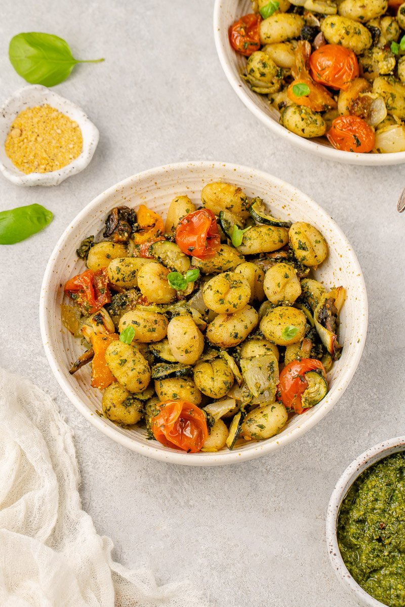 pesto gnocchi with vegetables in a white speckled bowl