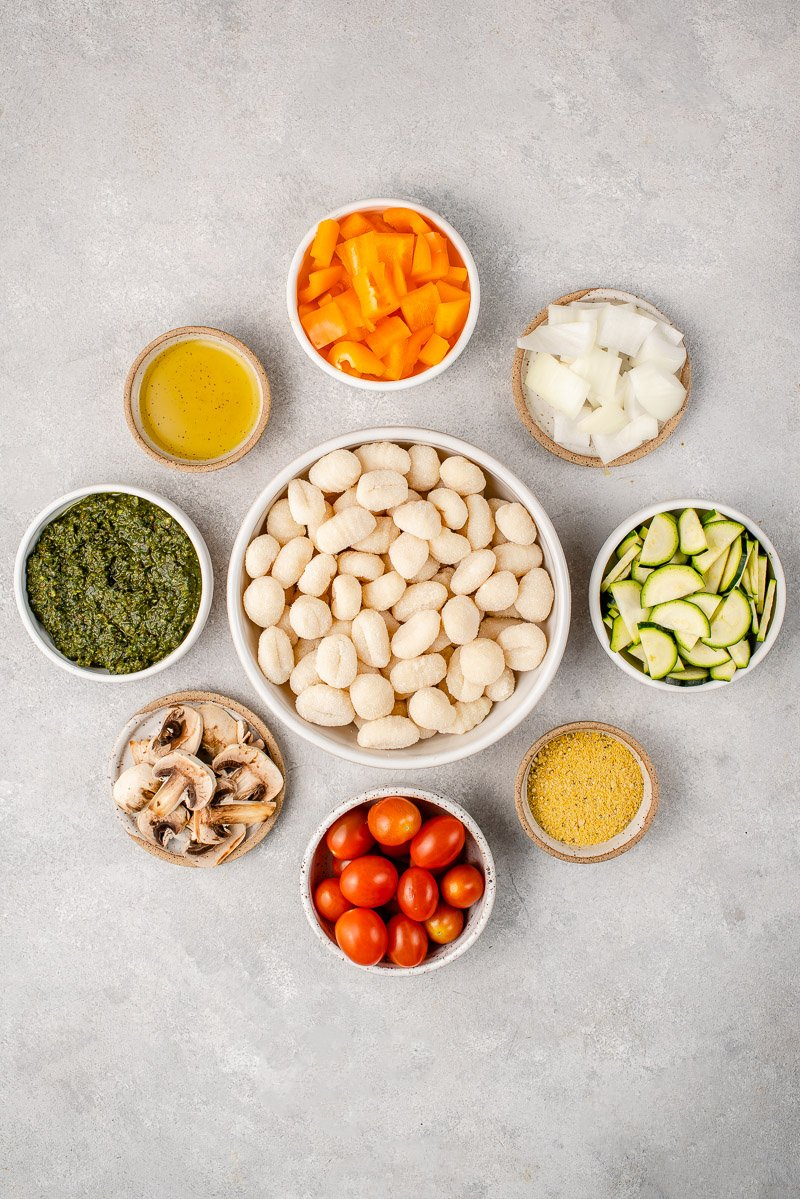ingredients for pesto gnocchi in white bowls in a circle