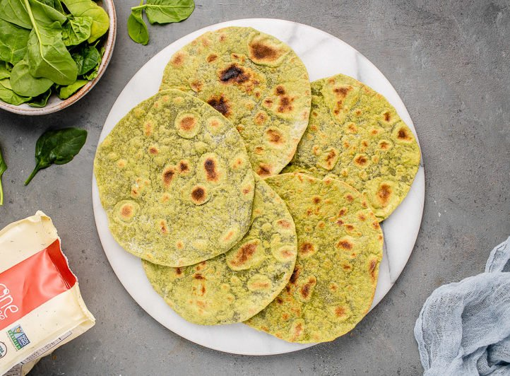 close up of whole wheat spinach tortillas on a marble board surrounded by ingredients