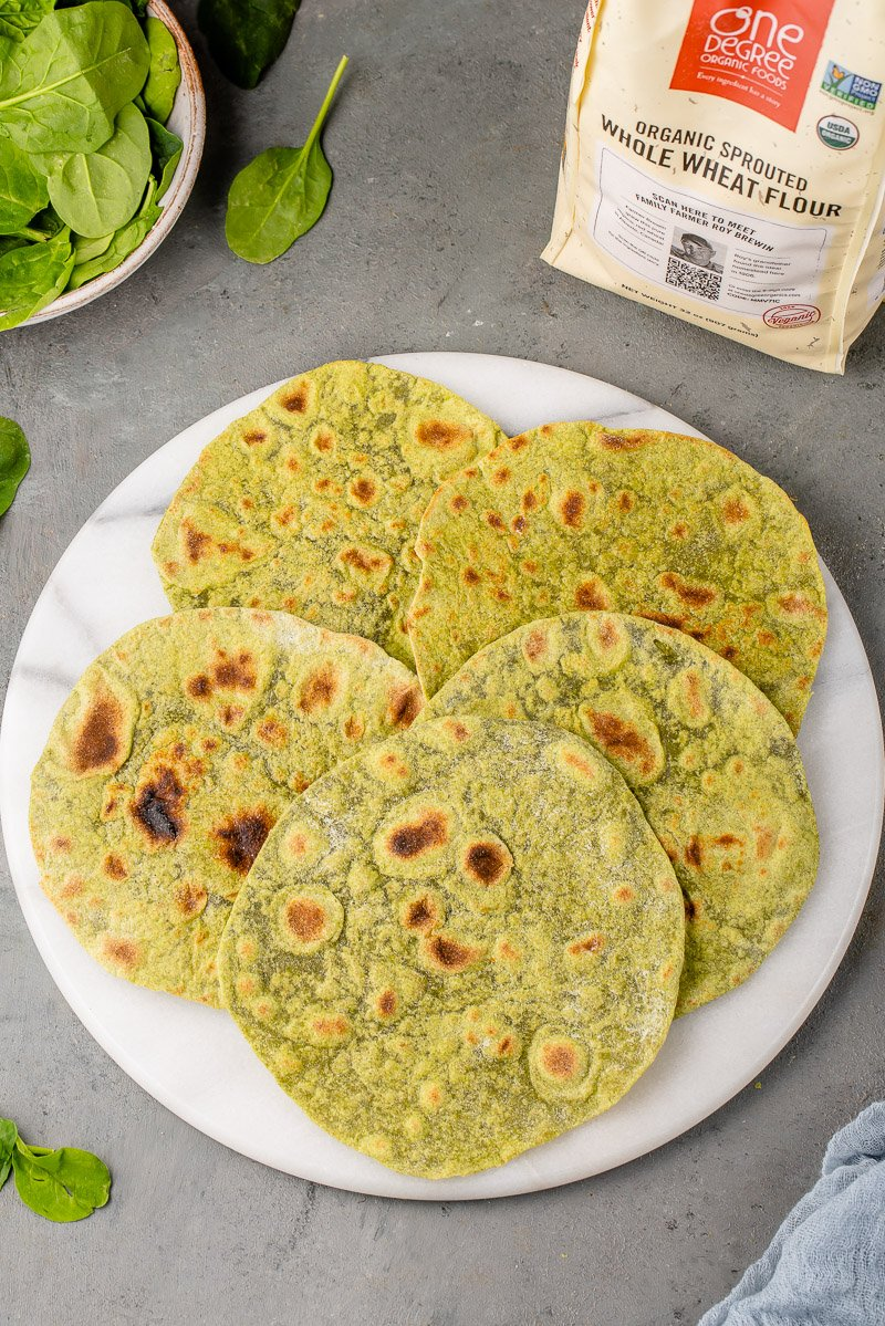 whole wheat spinach tortillas on a marble board surrounded by ingredients