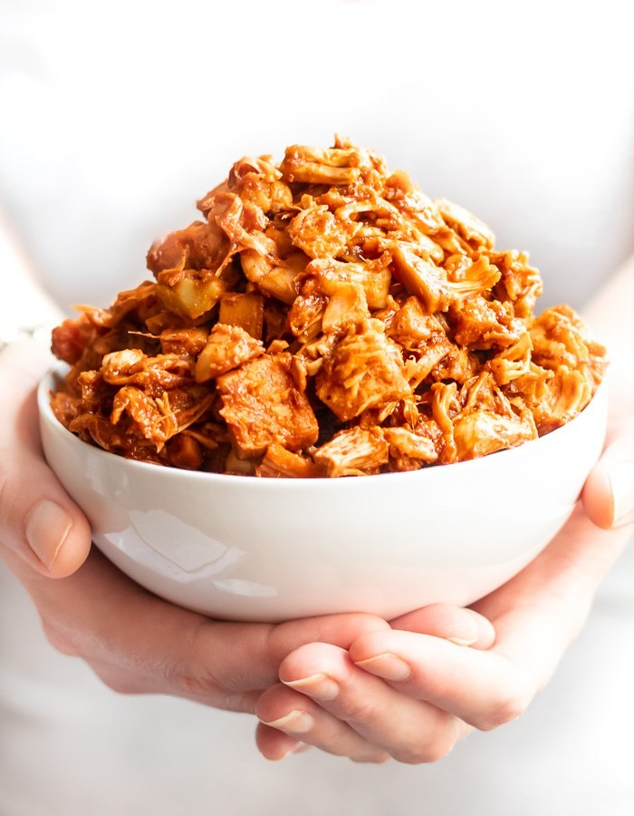 macro image of heaping bowl of BBQ jackfruit being held in hands.