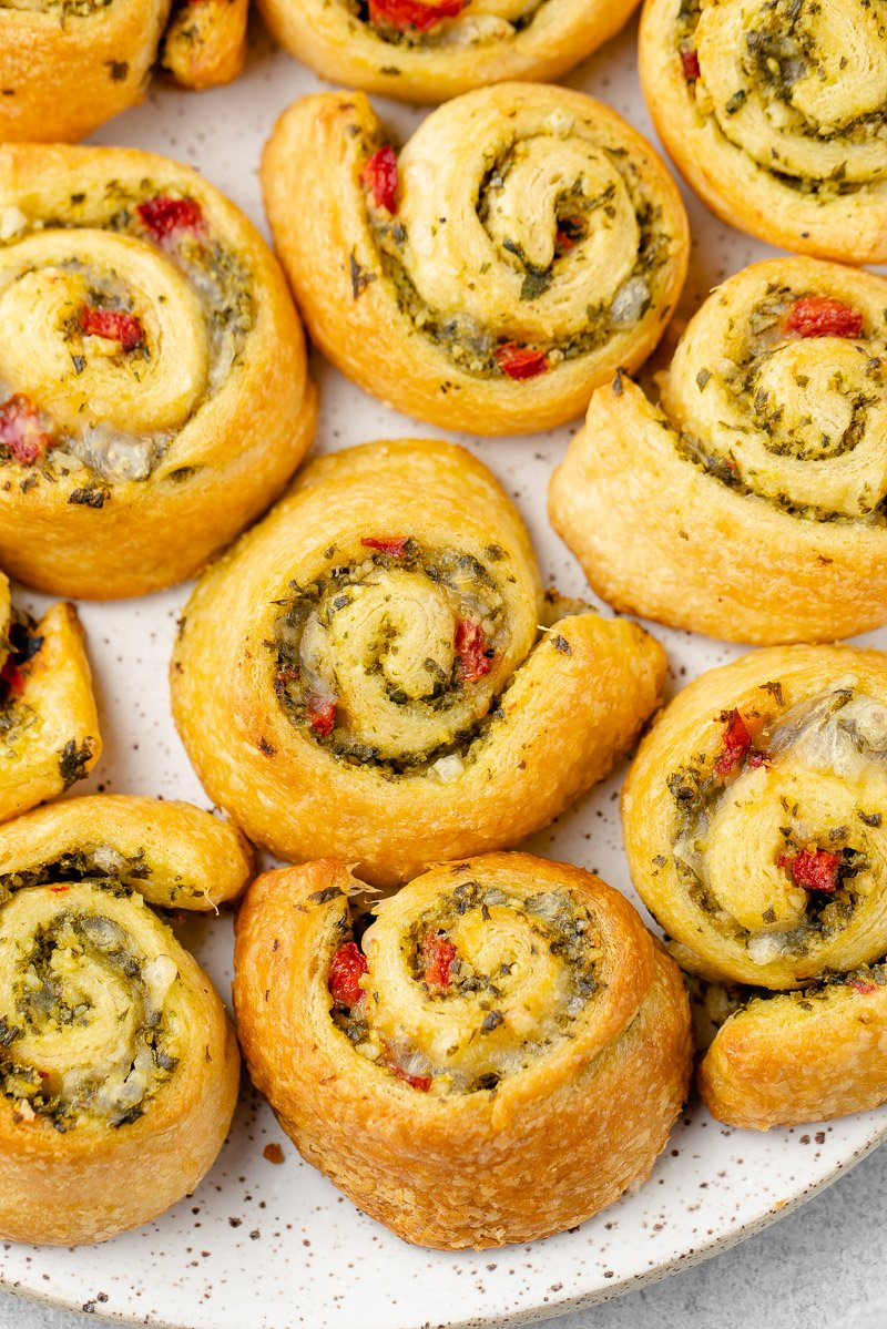 close up photo of vegan pesto pinwheels on a white speckled plate