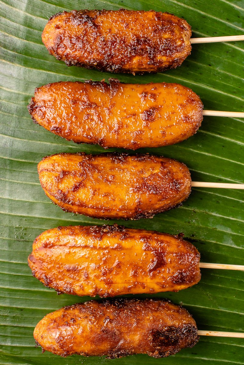 a photo of caramelized bananas on barbecue sticks laying on a banana leaf
