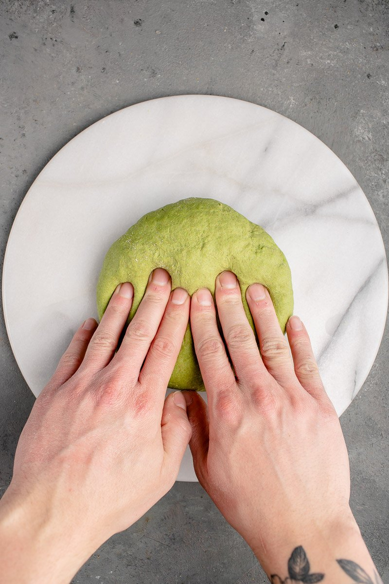 kneading green dough for spinach tortillas on marble board