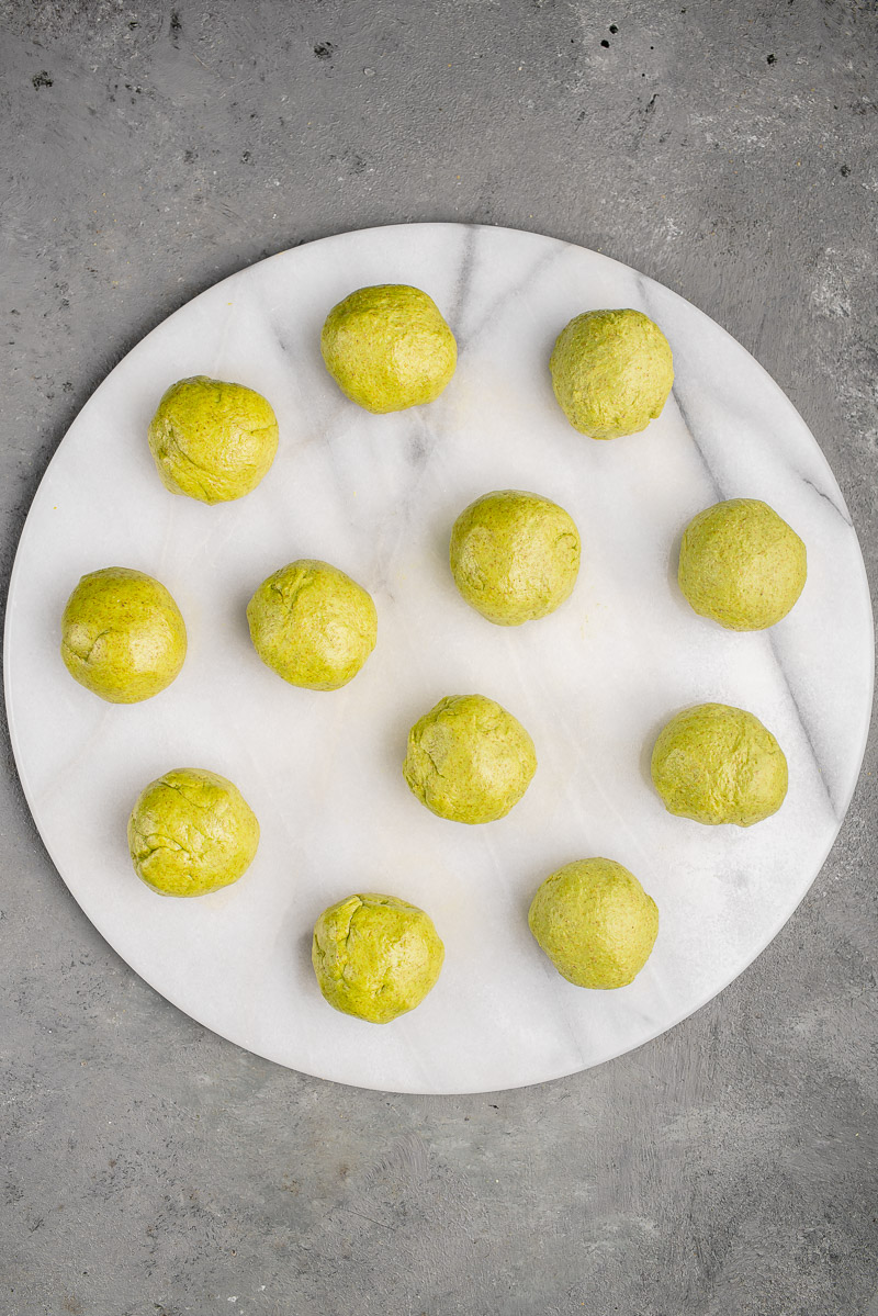 small green dough balls for spinach tortillas on marble board