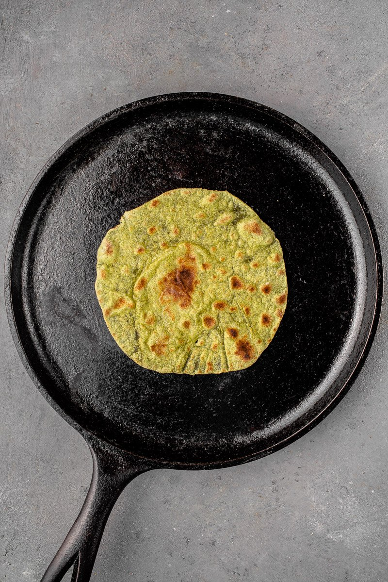 green spinach tortilla cooking on cat iron griddle