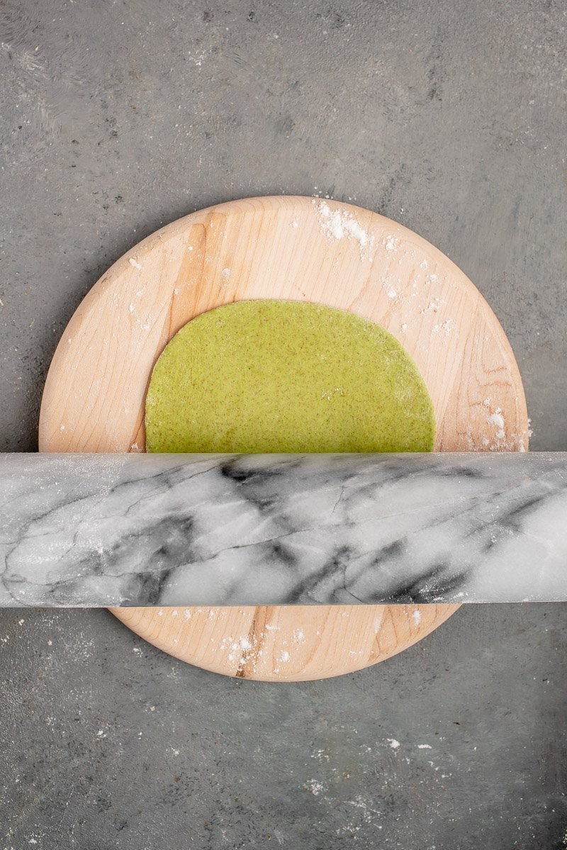 rolling out green dough for spinach tortillas on wooden board