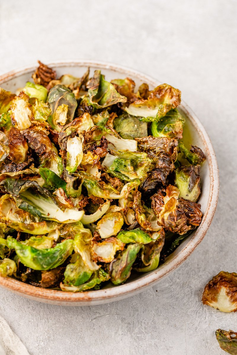 macro image of cooked brussels sprout chips in a bowl